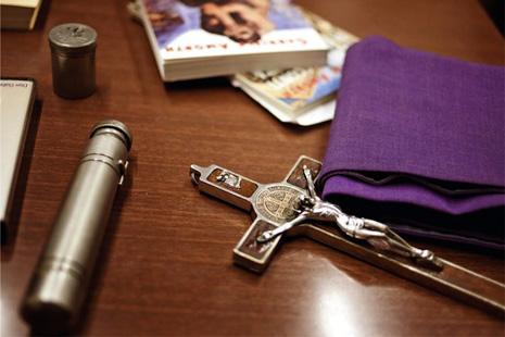 驅魔神父常用的工具:一小瓶聖水、一個刻有聖本篤印章的苦像,以及紫色祭帶。