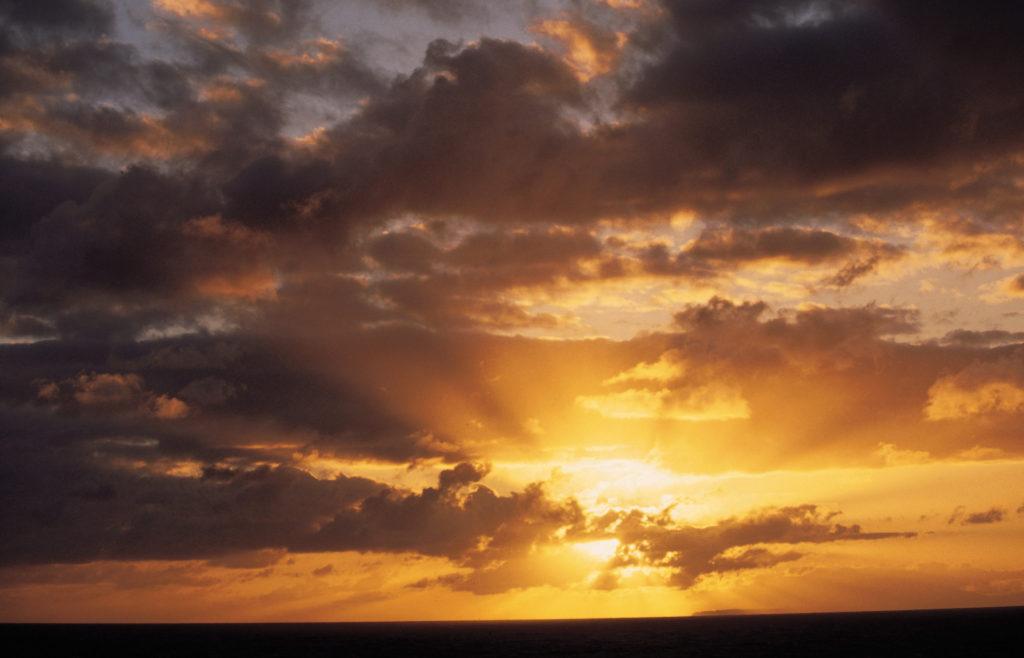 Sun rising behind clouds , Oahu , Hawaii