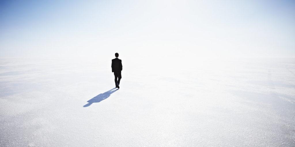 Businessman walking along empty landscape