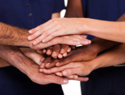 multiracial hands together to form teamwork